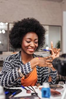 Чувствовать себя великолепно. красивая темнокожая женщина чувствует себя счастливой, пробуя новые яркие образцы