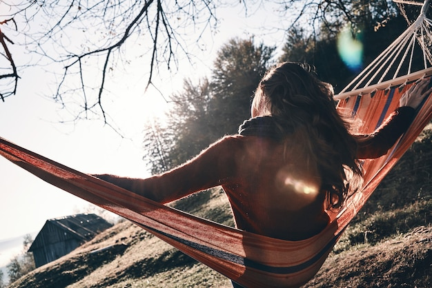 Feeling great.  rear view of young woman keeping arms outstretched while relaxing in hammock outdoors