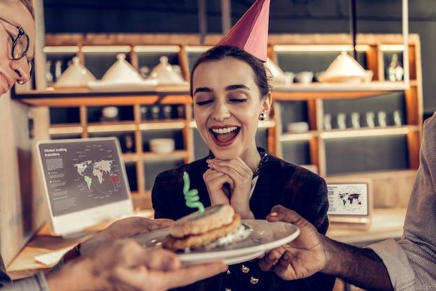 幸せを感じます。ハンバーガーを見ながらあごの下で手をつないで陽気なブルネットの女の子