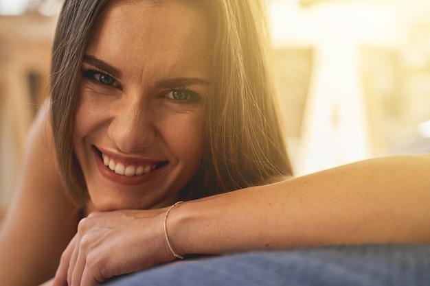 행복을 느낀다. 그녀의 미소를 시연하면서 침대에 그녀의 팔꿈치를 기대어 긍정적인 기쁨 여성 사람