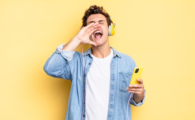 Чувствует себя счастливым, взволнованным и позитивным, громко кричит, прижав руки ко рту, выкрикивая. наушники и смартфон концепция
