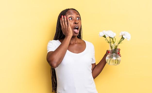 두 손으로 얼굴을 짚고 옆을 바라보며 행복하고 설렘과 놀라움을 느낍니다. 장식 꽃 개념