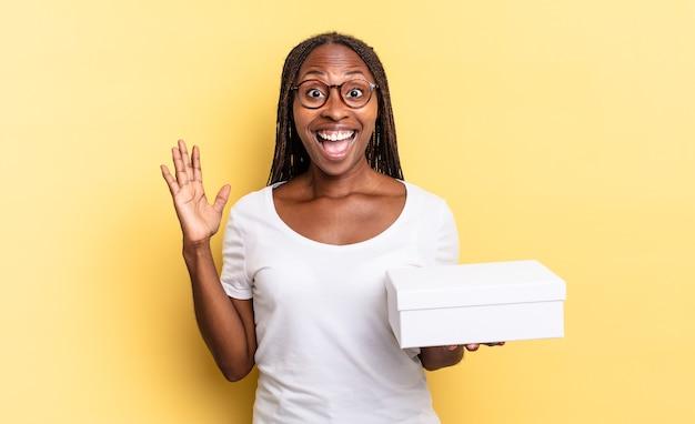 幸せ、興奮、驚き、ショックを感じ、信じられないほどの何かに微笑んで驚いて、空の箱を持っている