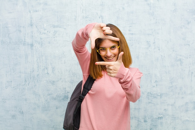 幸せで、友好的で、前向きで、笑顔で、手でポートレートやフォトフレームを作る