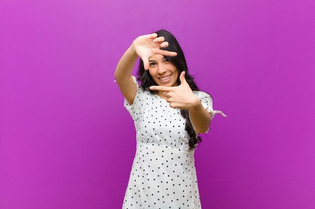 幸せで、フレンドリーで、前向きで、笑顔で、手でポートレートやフォトフレームを作る