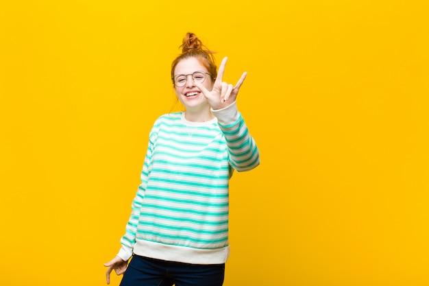 Чувствуя себя счастливым, веселым, уверенным, позитивным и бунтарским, делая знак рок или хэви-метал рукой Premium Фотографии