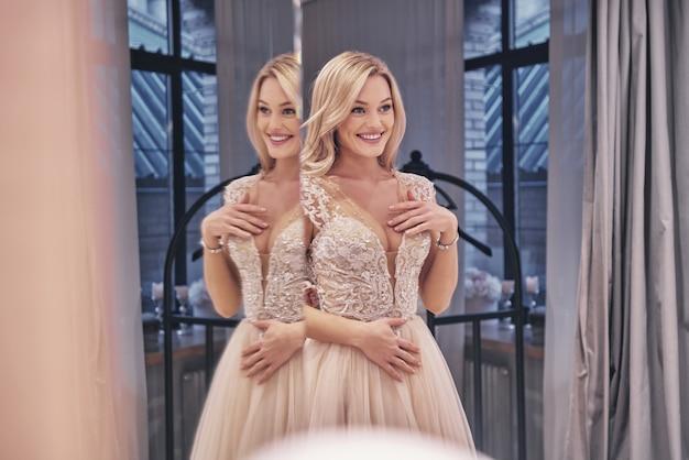 행복한 느낌. 웨딩 드레스를 입고 신부 가게에서 거울 앞에 서있는 동안 웃는 아름다운 젊은 여성의 반영