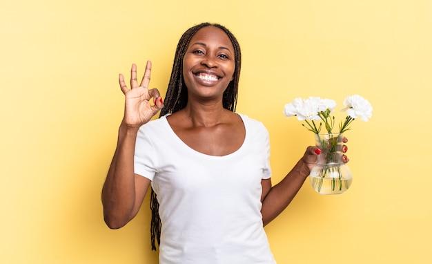 행복하고, 편안하고 만족하며, 괜찮은 제스처로 승인을 표시하고 미소를 짓습니다. 장식 꽃 개념