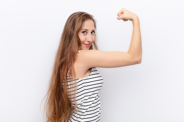 Feeling happy, satisfied and powerful, flexing fit and muscular biceps, looking strong after the gym