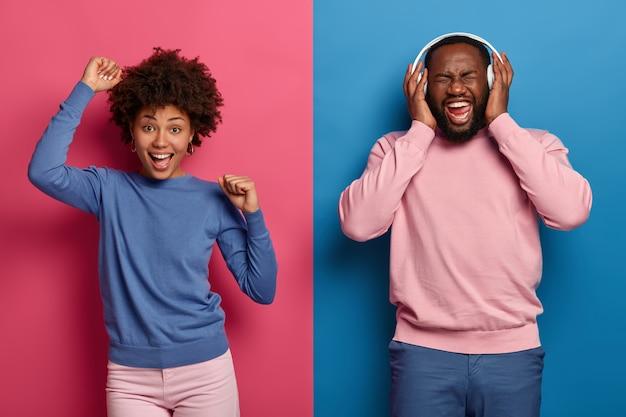 Sentirsi felice e ottimista. la donna afroamericana rilassata allegra balla sopra lo spazio rosa con le mani in alto