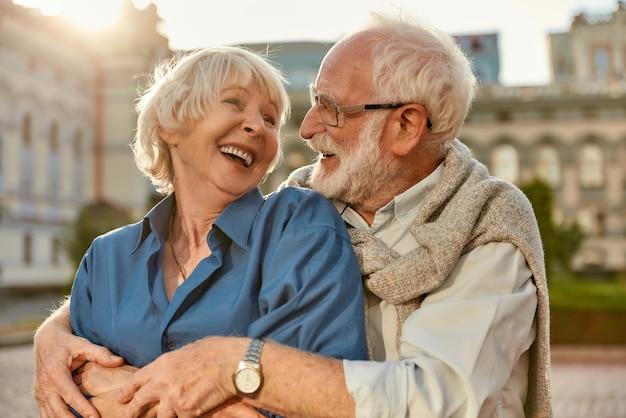 캐주얼 옷을 입고 서로 껴안고 웃고 있는 쾌활한 노부부와 함께 행복한 느낌