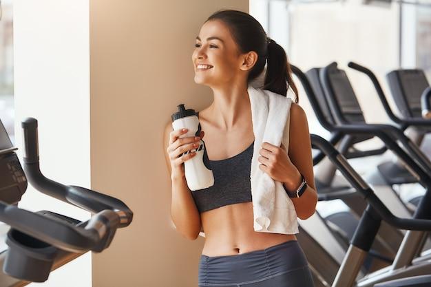 彼女の肩に白いタオルでスポーツウェアで幸せな若くて美しい女性を感じています