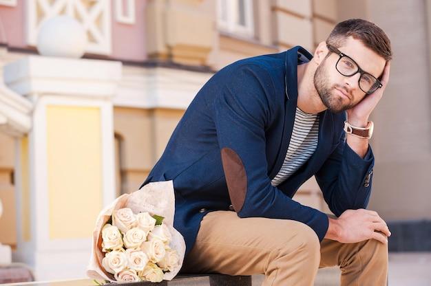 彼女が来ることについて絶望的な気持ち。花の花束が彼の近くに横たわっているベンチに座っている間、彼の頭を手に傾けてスマートジャケットを着た欲求不満の若い男