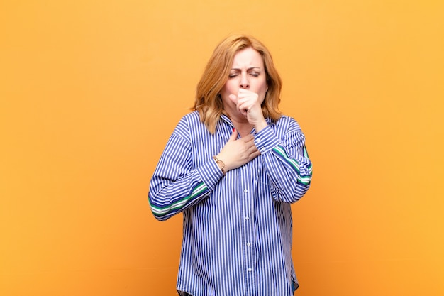 Feeling ill with a sore throat and flu symptoms, coughing with mouth covered