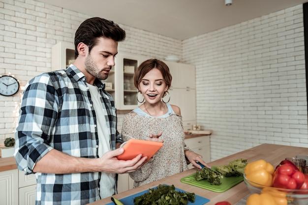 興味を持っています。キッチンで朝食を調理しながらインターネットで写真を見て大きなイヤリングを持つ若いきれいな女性