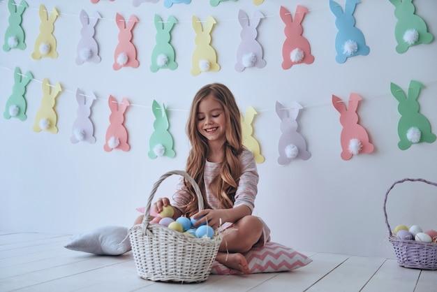 휴가에 대한 기쁨을 느낍니다. 부활절 바구니를 가지고 놀고 배경에 장식이 있는 베개에 앉아 웃는 귀여운 소녀