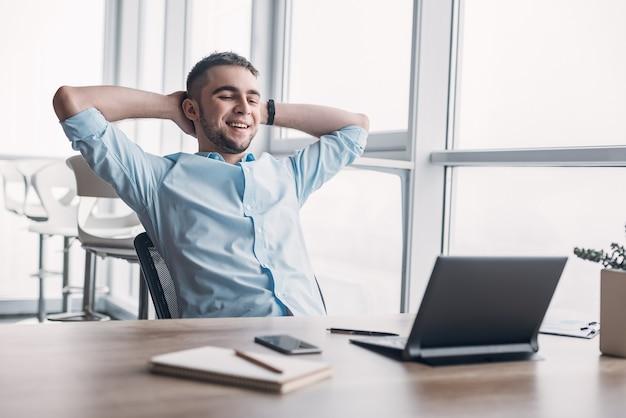 Ощущение радости. веселый молодой кавказский бизнесмен откидывается на стуле и держит руки за головой, глядя на экран с широкой улыбкой