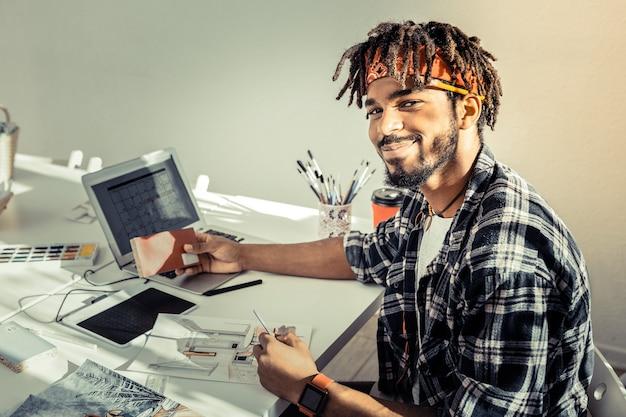 うれしそうな気持ち。彼の絵画スタジオで働いている間、喜びと陽気を感じているハンサムなアーティスト