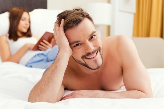 그냥 행복한 느낌. 잘생긴 젊고 셔츠를 입지 않은 남자가 침대에 누워 웃고 있는 동안 여자가 배경에서 책을 읽는 동안