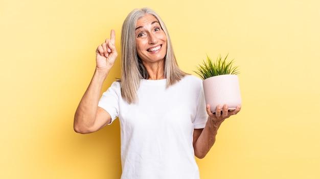 アイデアを実現した後、幸せで興奮した天才のように感じ、元気に指を上げて、エウレカ!観賞植物を持っています