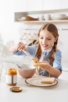 Feeling like a chef. excited active stunning child putting a lot of creamy delicious peanut butter on the bread while making sandwiches for herself and her little brother