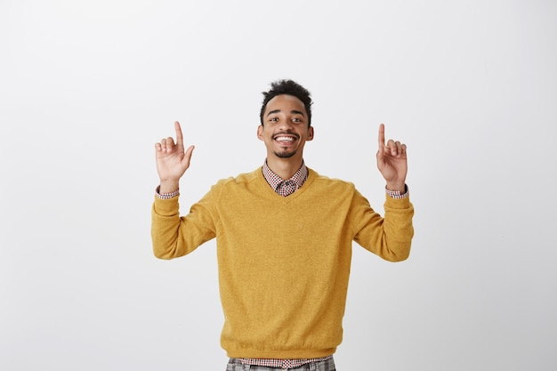 Feeling like winner. portrait of satisfied happy african-american guy in yellow pullover, raising index fingers and pointing upwards, being pleased with positive result, triumphing from good news