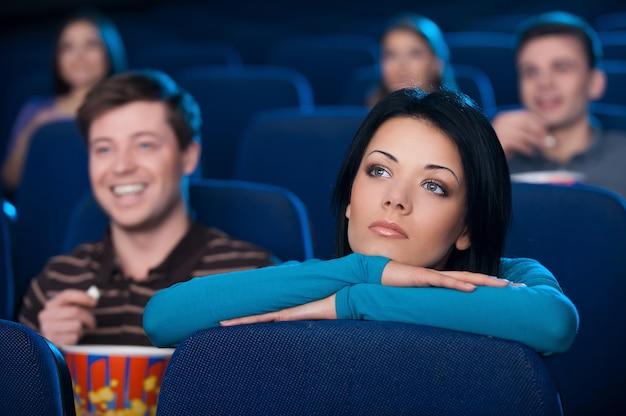 Чувствую себя одиноким в кино. скучно молодая женщина смотрит фильм в кинотеатре