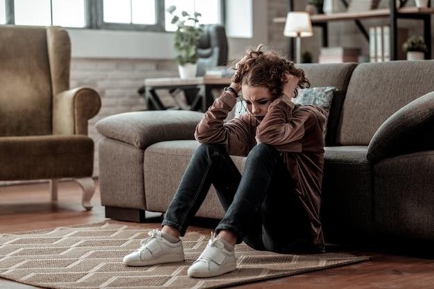 孤独に感じる。白いスニーカーを履いた巻き毛の 10 代の少女が、学校で問題を抱えて孤独と孤立を感じている