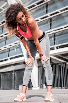 Чувство усталости. красивая привлекательная женщина наклоняется вперед во время отдыха после тренировки