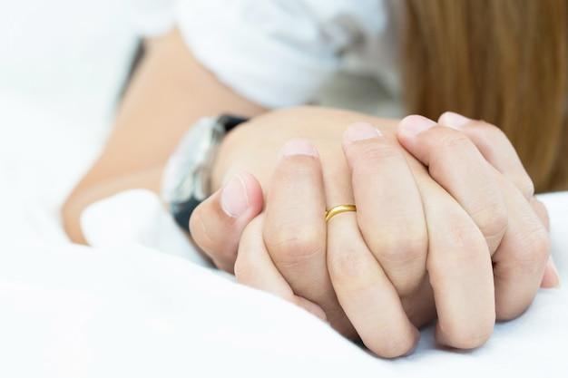 Чувство на руках страсти пара занимается сексом. двое влюбленных пара, держась за руки под одеялом белые простыни на кровати с похотью и занимаясь любовью. концепция, имеющая сексуальные романтические моменты.