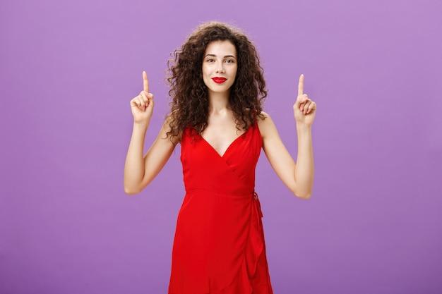 스타일리시한 메이크업을 완성한 후의 기분. 붉은 이브닝 드레스와 립스틱을 입은 귀엽고 부드러운 매력적인 유럽 여성은 짙은 곱슬머리가 부드럽게 웃고 손을 위로 가리키고 있습니다.