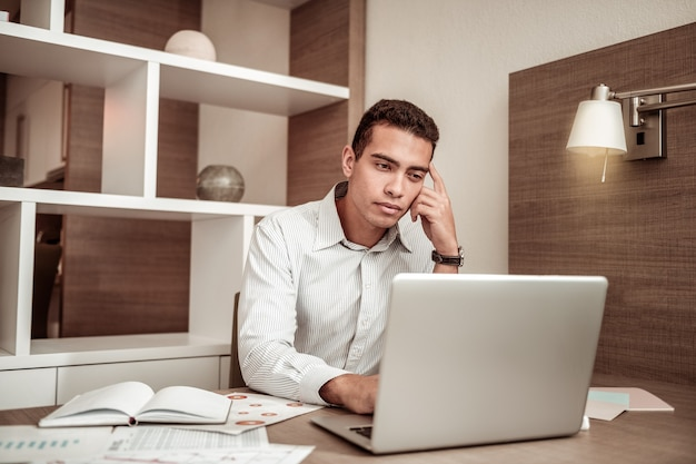Feeling overloaded. young dark-eyed businessman feeling overloaded while working on month report