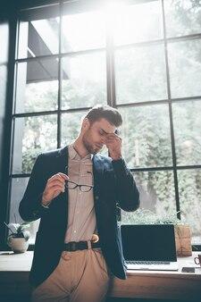 過労を感じています。目を閉じてオフィスの大きな窓の前に立っている間、眼鏡を持って鼻をマッサージしている欲求不満の若い男のローアングルビュー