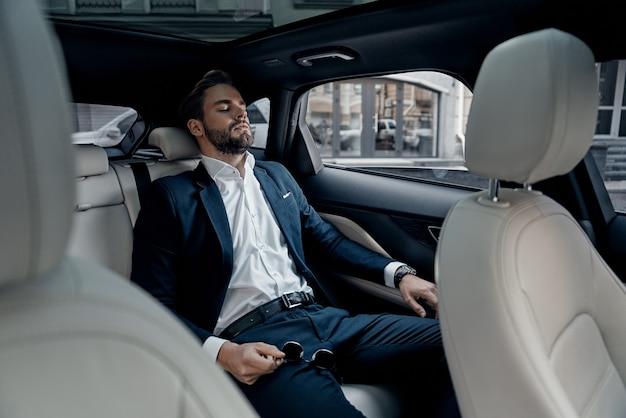과로한 느낌. 차에 앉아있는 동안 눈을 감고 전체 양복에 피곤된 젊은 남자