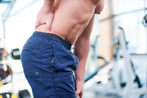 トレーニング後に痛みを感じる。ジムに立っているときに彼の背中を曲げて触れている筋肉の男のクローズアップ