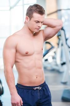 トレーニング後に痛みを感じる。ジムに立っている間、首に触れて否定性を表現する欲求不満の若い筋肉の男
