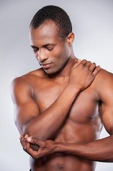 Ощущение боли в локте. молодой мускулистый африканский мужчина трогает его локоть, стоя на сером фоне