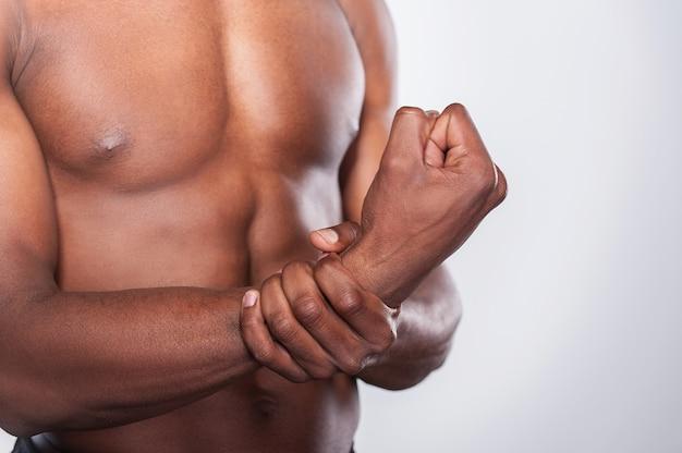 Ощущение боли в суставе. обрезанное изображение молодого мускулистого африканского мужчины, касающегося его руки, стоя на сером фоне