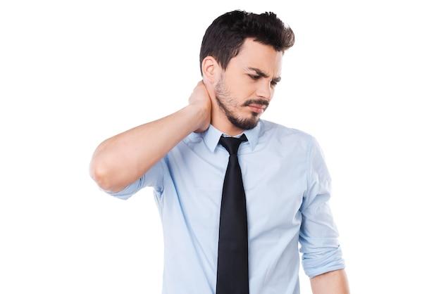 首の痛みを感じる。シャツとネクタイで首に触れて欲求不満の若い男