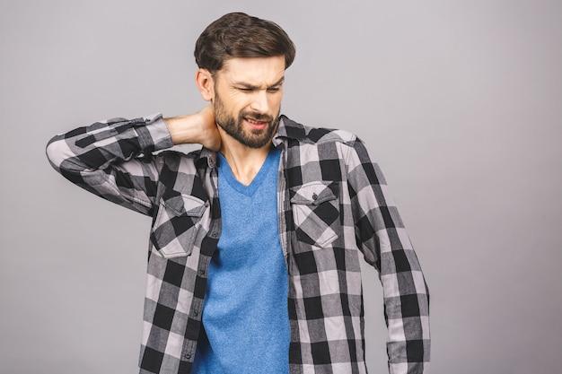 Ощущение боли в шее. разочарованный молодой человек случайно касаясь его шеи и выражая отрицательность стоя.