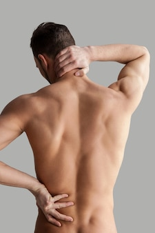Feeling pain. rear view of young muscular man touching his back while standing isolated on grey background