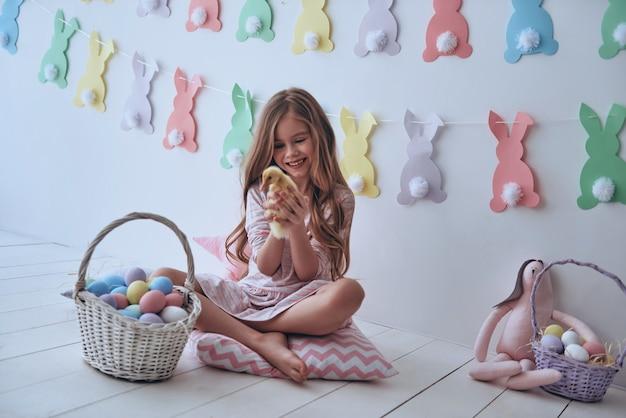 장난스런 느낌. 배경에 장식이 있는 베개에 앉아 있는 동안 오리와 놀고 웃고 있는 귀여운 소녀