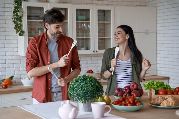 Feeling playful young happy family couple husband and wife having fun while preparing healthy food