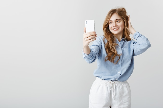 Feeling pretty and confident today. portrait of pleased attractive feminine female student in blue blouse checking hairstyle while taking selfie with smartphone, smiling broadly over gray wall