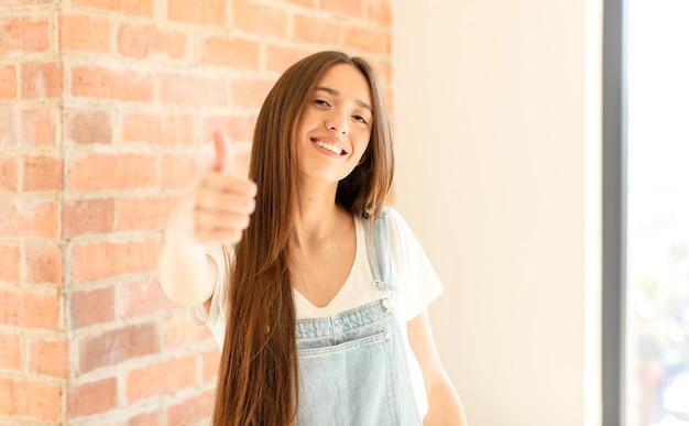 자랑스럽고 평온하고 자신감 있고 행복하며 엄지 손가락으로 긍정적으로 웃고 있습니다.