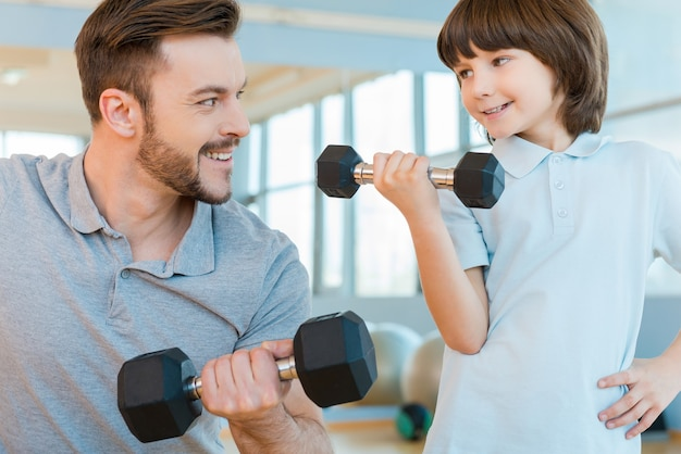 彼の息子を誇りに思っている。幸せな父と息子がダンベルで運動し、一緒にヘルスクラブに立っている間笑顔