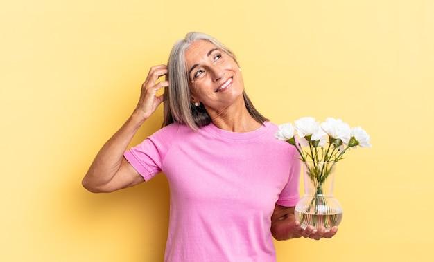 戸惑い、混乱し、頭をかいて、飾り花を持って横を向いている