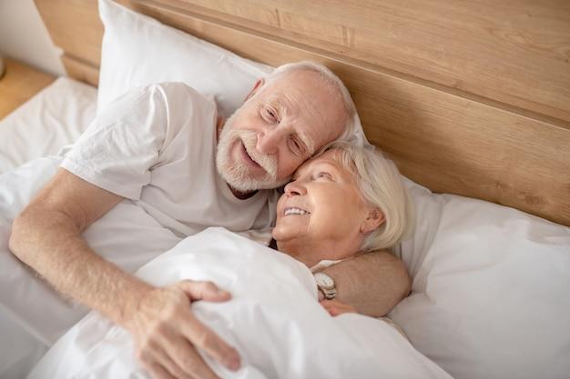リラックスした気分。ベッドに横になってリラックスして見える老夫婦