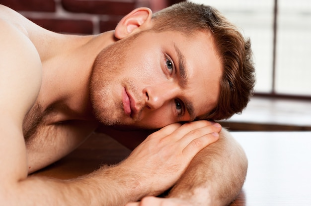 リラックスした気分。テーブルに寄りかかってカメラを見ているハンサムな若い上半身裸の男