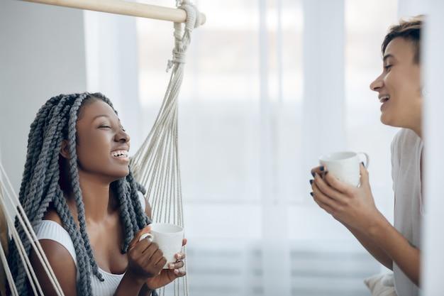 Чувство расслабленности. две девушки пьют кофе в светлой комнате и выглядят расслабленными